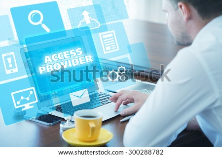 Business, technology, internet and networking concept. Young businessman working on his laptop in the office, select the icon access provider on the virtual display - stock photo