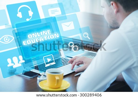 Business, technology, internet and networking concept. Young businessman working on his laptop in the office, select the icon online education on the virtual display. - stock photo