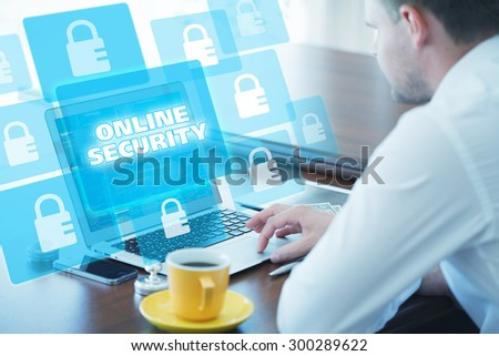 Business, technology, internet and networking concept. Young businessman working on his laptop in the office, select the icon online security on the virtual display. - stock photo