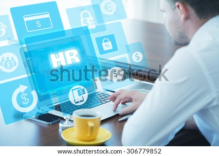 Business, technology, internet and networking concept. Young businessman working on his laptop in the office, select the icon  HR â?? Human Resources on the virtual display. - stock photo