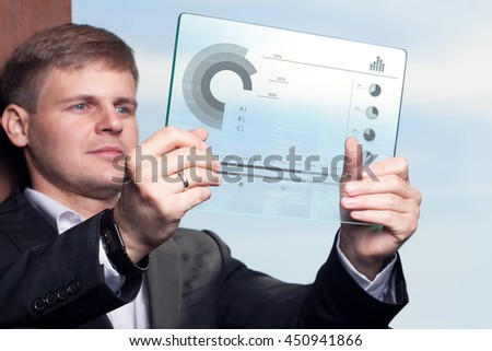 Business, technology, internet and networking concept. Young businessman working on his tablet in the office