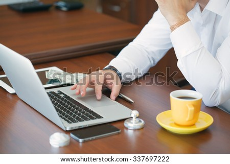 Business, technology, internet and networking concept. Young male businessman sitting at a desk in the office. - stock photo