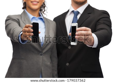 business, technology, internet and office concept - businessman and businesswoman with blank black smartphone screens in office - stock photo