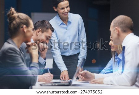 business, technology, management and people concept - smiling female boss talking to business team in office - stock photo