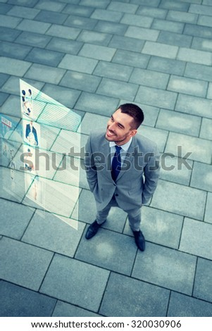 business, technology, mass media and people concept - young smiling businessman reading information from virtual screen outdoors - stock photo