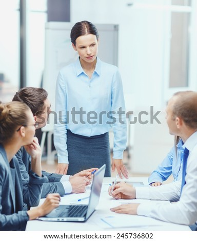 business, technology, people and management concept - strict female boss talking to business team in office - stock photo