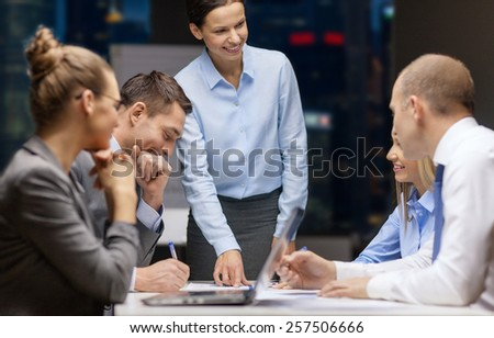 business, technology, people, deadline and team work concept - smiling female boss talking to business group at night office background - stock photo