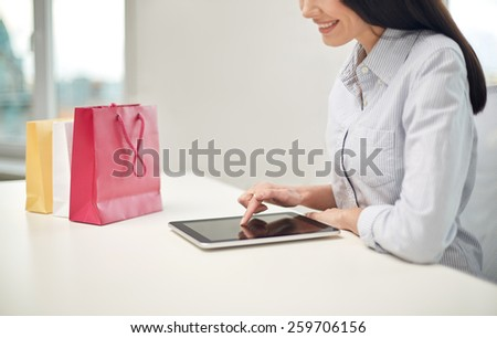 business, technology, sale, communication and people concept - close up of woman with tablet pc computer and shopping bags at office or home