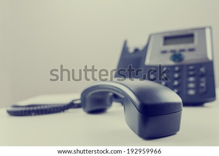 Business telephone handset with base station in the background. - stock photo