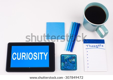 Business Term / Business Phrase on Tablet PC - Blues, cup of coffee, Pens, paper clips Calculator with a blue note pad on White - White Word(s) on blue - Curiosity - stock photo