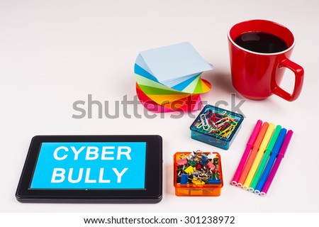 Business Term / Business Phrase on Tablet PC - Colorful Rainbow Colors, Cup, Notepad, Pens, Paper Clips, White surface - White Word(s) on a cyan background - Cyber Bully - stock photo
