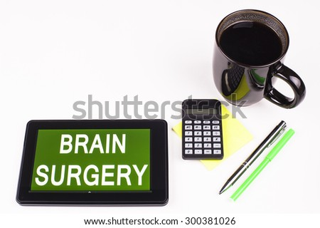 Business Term / Business Phrase on Tablet PC - Cup of coffee, Pens, Calculator and a green/yellow note pad on a White surface - White Word(s) on a green background - Brain Surgery - stock photo