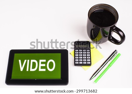 Business Term / Business Phrase on Tablet PC with a cup of coffee, Pens, and Calculator with a green/yellow note pad on a White Background - White Word(s) on a green background - Video - stock photo
