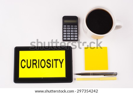 Business Term / Business Phrase on Tablet PC with a cup of coffee, Pens, Calculator, and yellow note pad on a White Background - Black Word(s) on a yellow background - Curiosity - stock photo