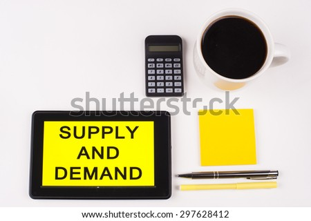 Business Term / Business Phrase on Tablet PC with a cup of coffee, Pens, Calculator, and yellow note pad on a White Background - Black Word(s) on a yellow background - Supply And Demand - stock photo