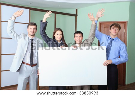 Business theme: business people holding empty billboard. Shot in an office. - stock photo