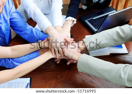 Business theme: hands on top of each other. - stock photo