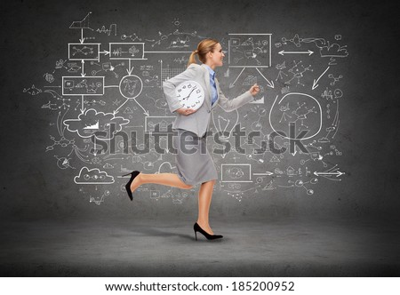business, time and education concept - smiling young businesswoman with clock running - stock photo