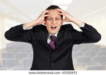 Business trainer or lecturer getting crazy before presentation in auditorium - stock photo