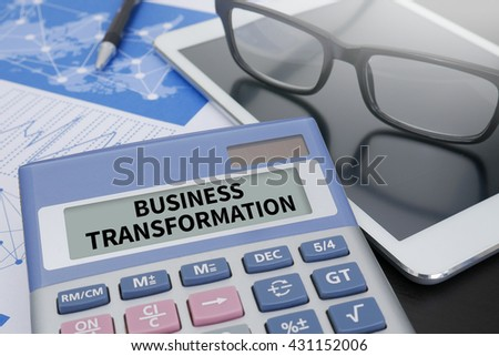 BUSINESS TRANSFORMATION Calculator  on table with Office Supplies. ipad