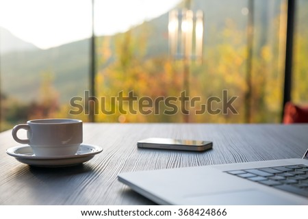 Business Travel Composition with cropped Computer Coffee Mug and Telephone on black grey Wood Table and large Windows Garden and Mountains on Background