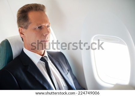 Business travel. Confident mature businessman sitting at his seat in airplane  - stock photo