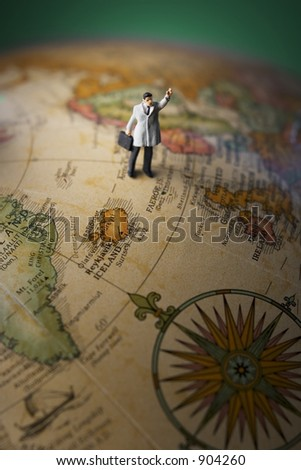Business travel figure on globe with green background and spotlight - stock photo