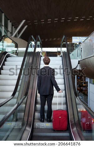business travel, man with luggage on escalator in airport - stock photo