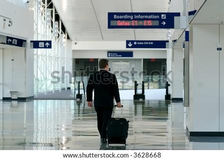 Business traveler walking thru airport terminal - stock photo