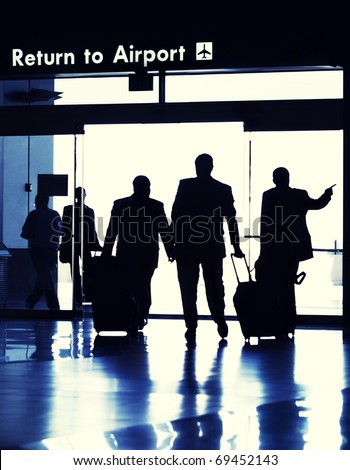 Business travelers exiting Airport terminal.  Image Cross Processed. - stock photo