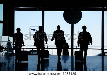 Business travelers silhouette moving in airport - stock photo