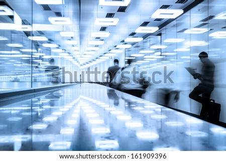 Business travelers  walking along contemporary illuminated airport terminal hall. - stock photo