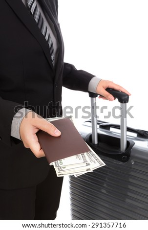 Business traveling pulling suitcase and holding passport - stock photo