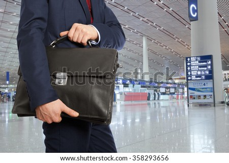 Business trip. Businessman with a briefcase in airport - stock photo