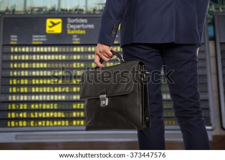 Business trip. Businessman with a briefcase on a background of departure board at airport - stock photo
