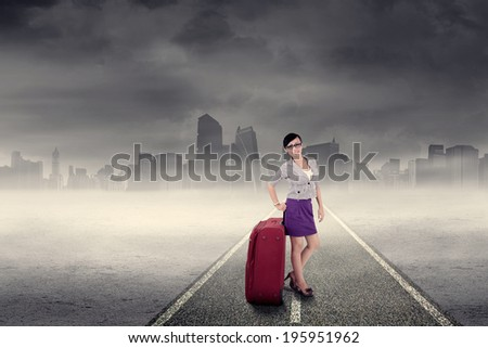 Business trip concept with a businesswoman standing on the road - stock photo