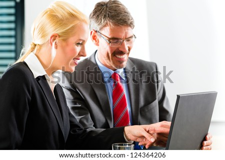Business - Two professionals in office in business attire looking at laptop screen working together - stock photo