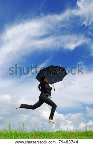 Business umbrella woman jumping to blue sky in grassland with black umbrella - stock photo