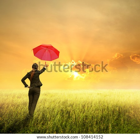 Business umbrella woman standing to sunset in grassland with red umbrella - stock photo