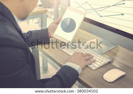 business using tablet and computer and looking chart - stock photo