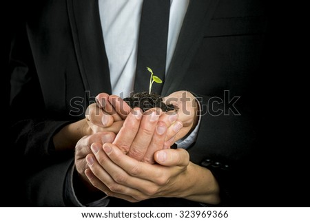 Business vision, start up  or teamwork concept - male and female business partners cupping a green sprout in a pinch of fertile soil. - stock photo