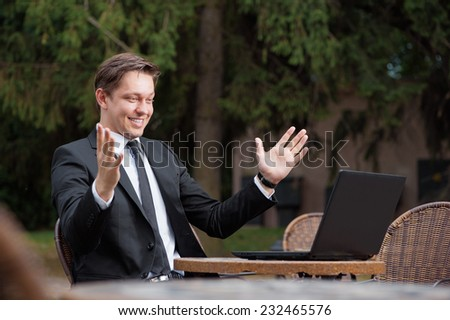 Business winner. Happy young caucasian man in suit and tie keeping arms raised and expressing positivity while sitting at the  outdoors cafe working with laptop with park at the background - stock photo