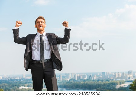 Business winner. Happy young man in formalwear keeping arms raised and expressing positivity while standing outdoors with cityscape in the background - stock photo