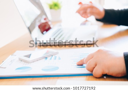 Business woman analyzing investment charts at morning time.