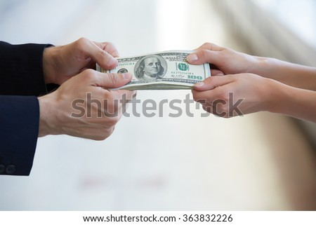 business woman and a businessman hold money