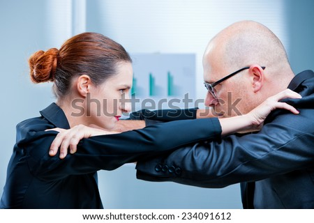 business woman and business man fighting facing each other - stock photo