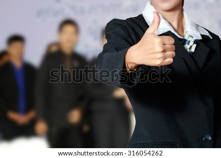 Business woman and business people thump up hand sign on business people background - stock photo