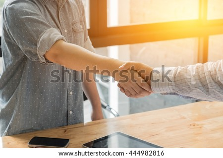 Business woman and partner shaking hands in office - stock photo