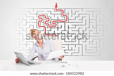 Business woman at desk with labyrinth in the background - stock photo