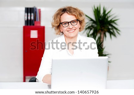 Business woman at office desk, working on laptop